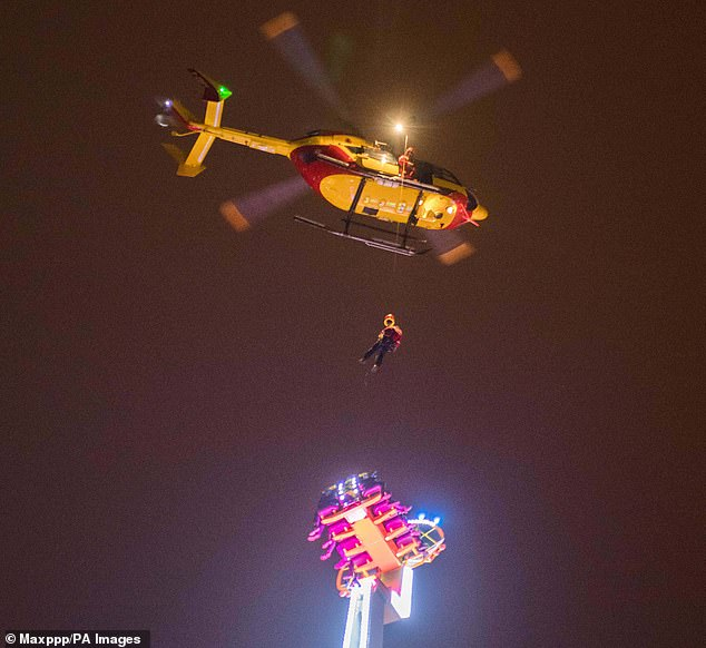Helping hand: Firefighters arrived, but their ladder only reached 100ft, so a helicopter was eventually called into help airlift some of the eight people stuck on the ride
