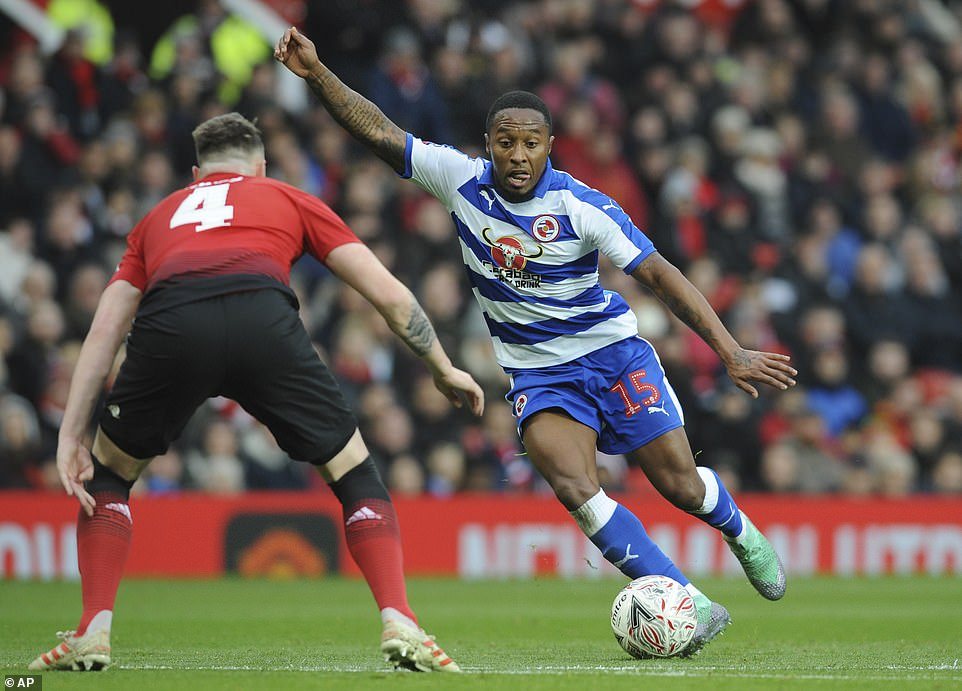 Manchester United defender Phil Jones is poised as Reading's Callum Harriott looks to fashion an opportunity