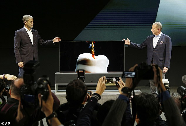 Tim Alessi, right, senior director of home entertainment product marketing, and David VanderWaal, vice president of marketing for LG Electronics USA, unveil the LG Signature OLED TV R during an LG news conference at CES