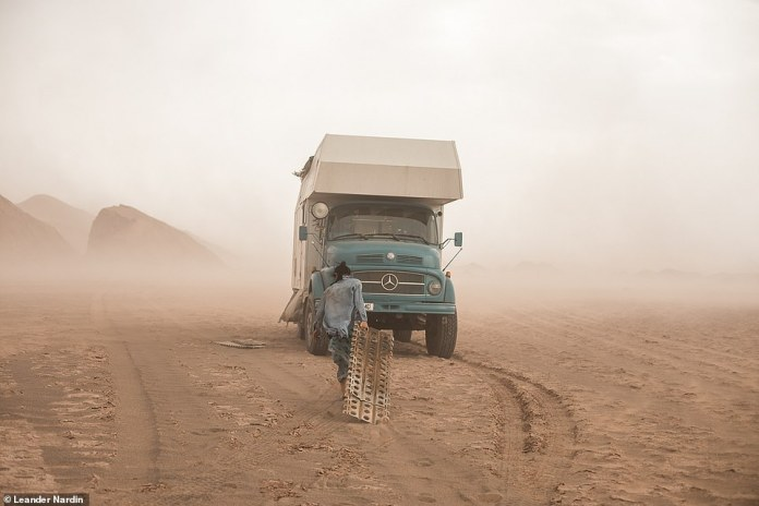 Maria returns to the truck during a dust storm in the Lut desert in Iran. The family documents their travels by posting images on their Instagram and Facebook pages, as well as on their blog, called Akela