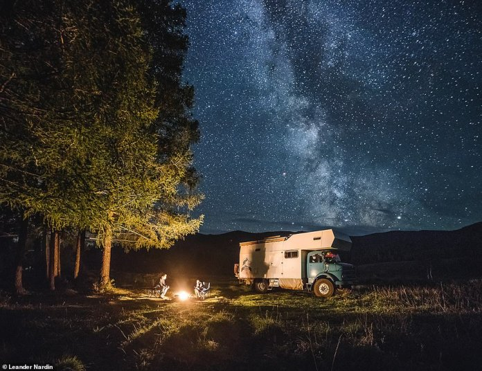 The family sits around a campfire under the stars after parking the truck in the Russian region of Altay, which is located in southern Siberia