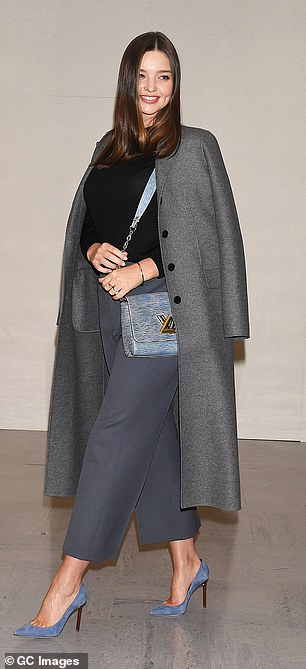 Chic traveller:The supermodel, 35, looked effortlessly elegant in impeccable tailoring, teaming navy blue high-waisted cropped trousers with a simple black crew-neck sweater