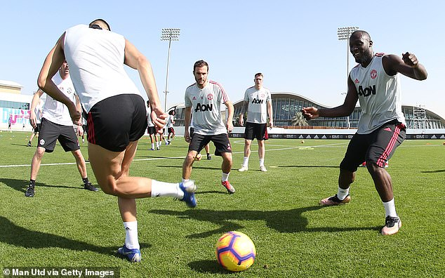 Romelu Lukaku (right) smiles as United's players take part in a drill in the heat of Dubai