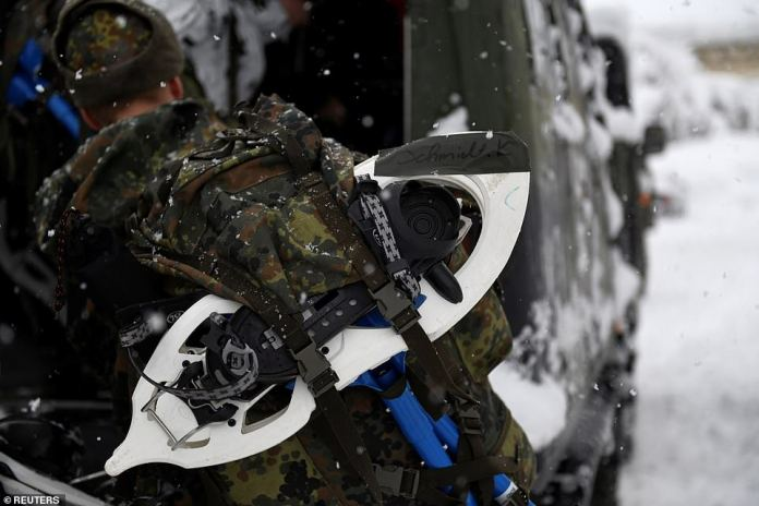 A soldier carries his snow shoes in Berchtesgaden ahead of work to remove snow from buildings in the town
