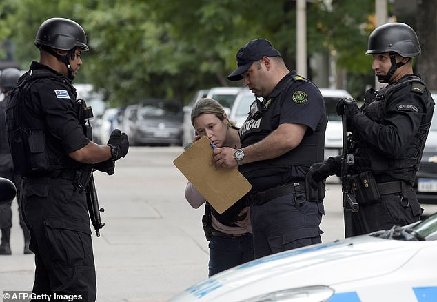 Officers discussing the situation during the long siege on Thursday as the man posted a Facebook video from inside