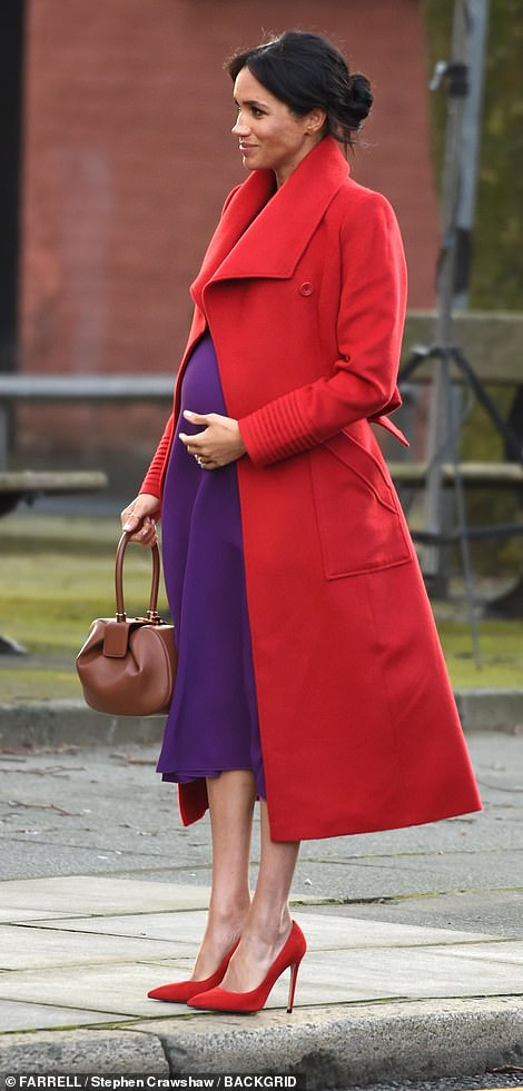 Meghan cradles her bump after touching down in Hamilton Square