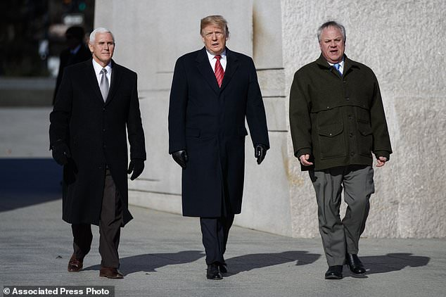 President Donald Trump, center, Vice President Mike Pence, left, escorted by Acting Interior Secretary David Bernhardt, right, visit the Martin Luther King Jr. Memorial, Monday, Jan. 21, 2019, in Washington.  (AP Photo/ Evan Vucci)