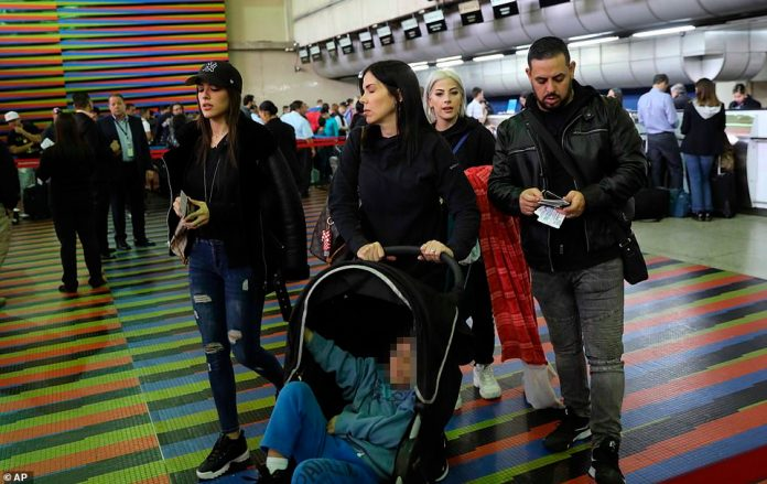 U.S. embassy employees and their families prepare to depart Simon Bolivar international airport in La Guaira, Venezuela, today amid the political turmoil in the country