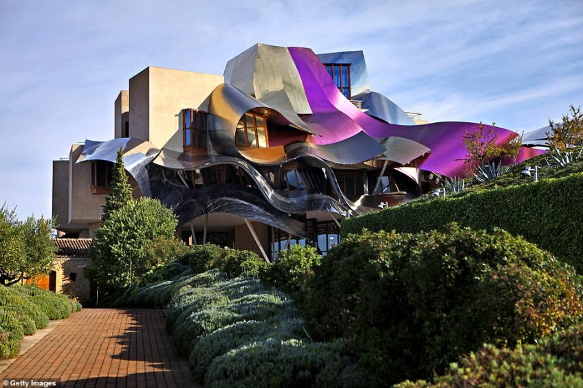 Tempranillo vines surround the colourful Marqués De Riscal Hotel in Elciego, Spain, which opened in 2006. It was designed by Frank Gehry and its pink-hued exterior is said to resemble a ribbon wrapped around a present. The hotel has 43 luxurious rooms and suites. The interior was also designed by Gehry