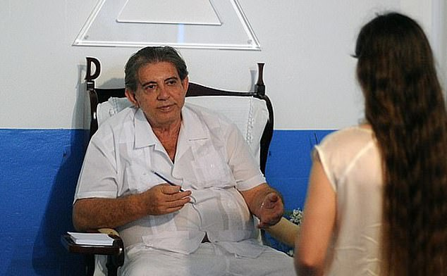 John of God, pictured with one of his patients, has been accused of sex abuse by hundreds of women and was arrested last year in Brazil
