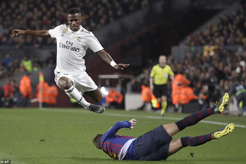 Pique flies across the ground to try and win the ball from Real Madrid's Vinicius Junior who jumps up to avoid the tackle
