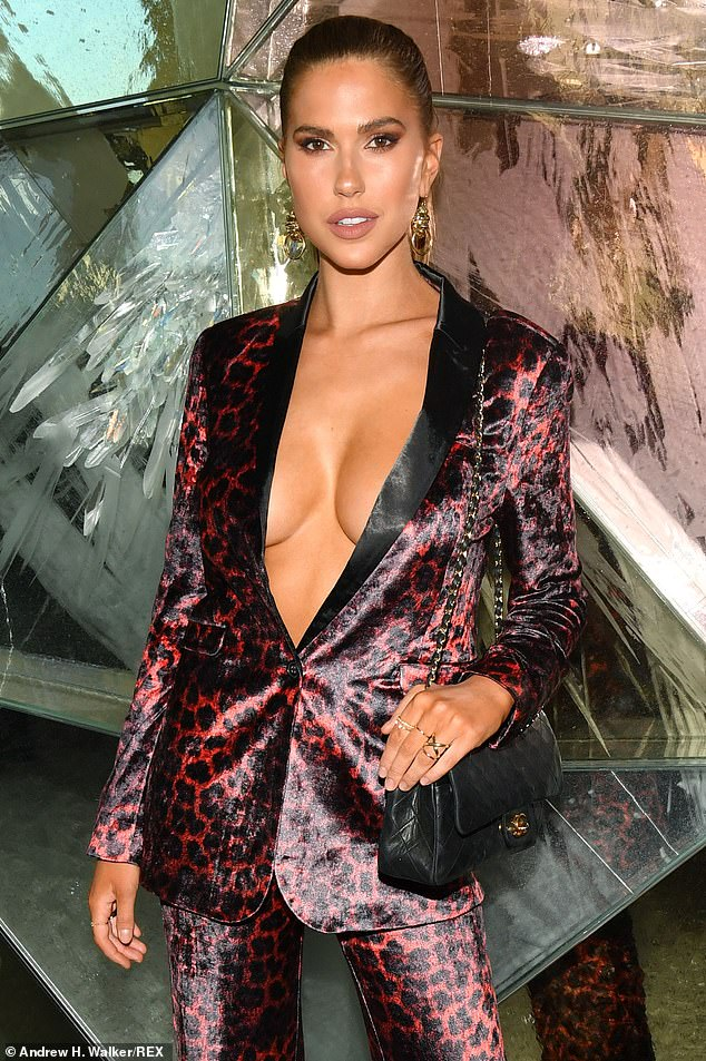 Radiant: Kara Del Toro bared her decolletage and a bit of her enviably trim midriff in a fitted red and black trouser suit with a leopard print