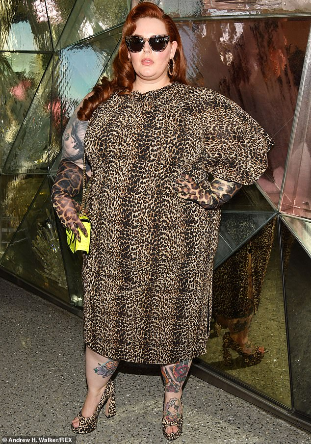 Wild side: Tess Holliday put her sprawl of arm tattoos on display in a half-sleeved leopard print dress, which was hemmed high enough to show off her calf body art as well