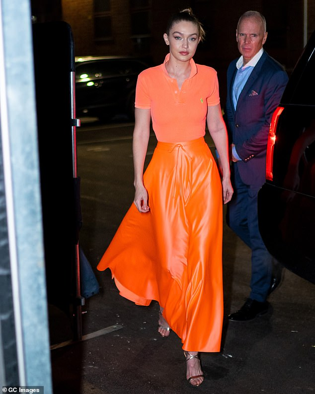 Fabulous:The elder sister of Bella Hadid slipped into a peach polo shirt that elegantly complemented her high-waisted gleaming orange skirt