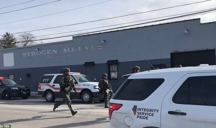 An armed law enforcement officer runs towards the Henry Pratt Warehouse in Aurora, Illinois