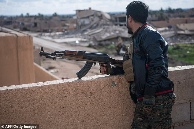 An armed member of the SDF stands guard atop a building in Baghouz, where the Kurdish-led coalition is fighting to expel ISIS from the last area of territory in Syria