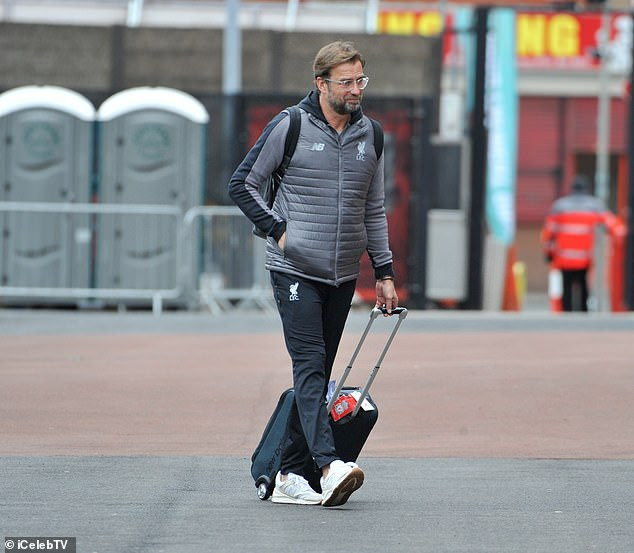 Jurgen Klopp wheels his suitcase into Anfield as Liverpool arrived on Tuesday afternoon