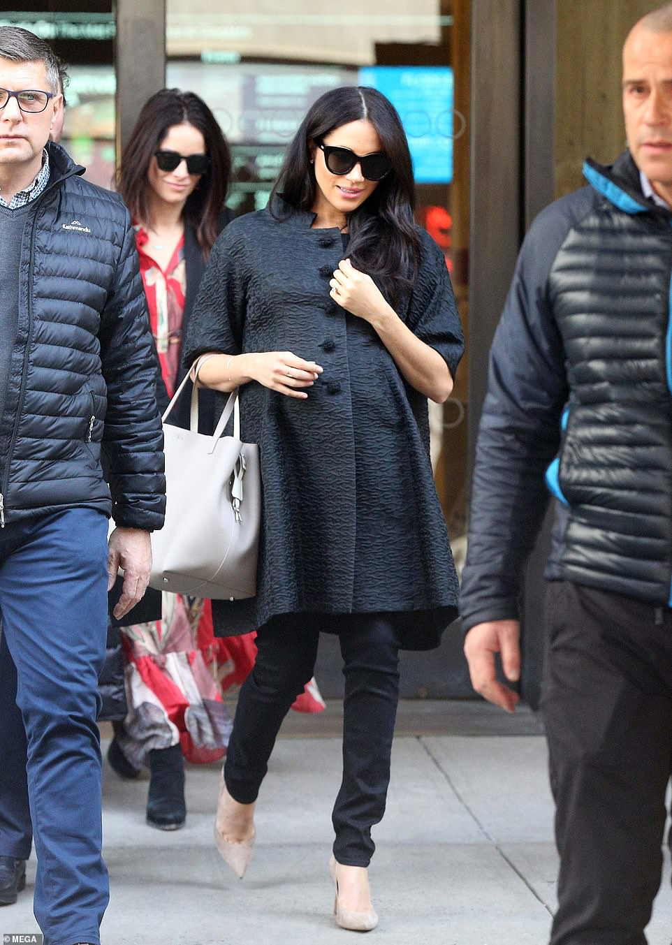 Watchful eye: Meghan and Abigail were flanked by two plain clothes officers as they made their way out of the Met Breuer, before crossing the street and heading into The Surrey hotel