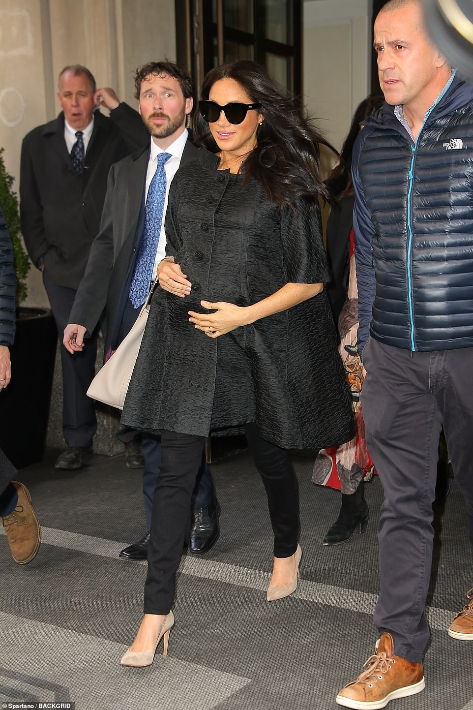 On the move: Meghan Markle was seen cradling her baby bump as she left the New York hotel where her baby shower is thought to be taking place, shortly after her guests began arriving