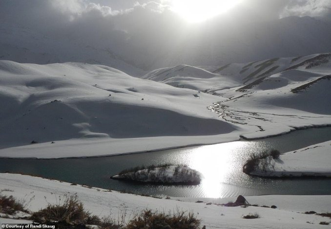 One image captures the breathtaking scenery in Iran, with undulating snowy peaks intersected by a snaking waterway