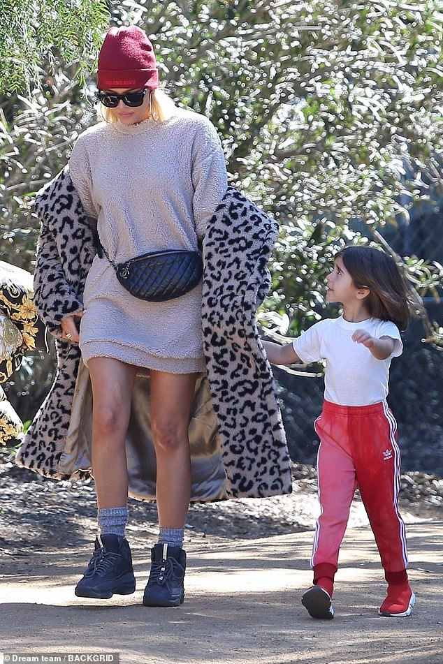 Sweet niece: Khloe is consoled by Kourtney's daughter Penelope, six, after the service