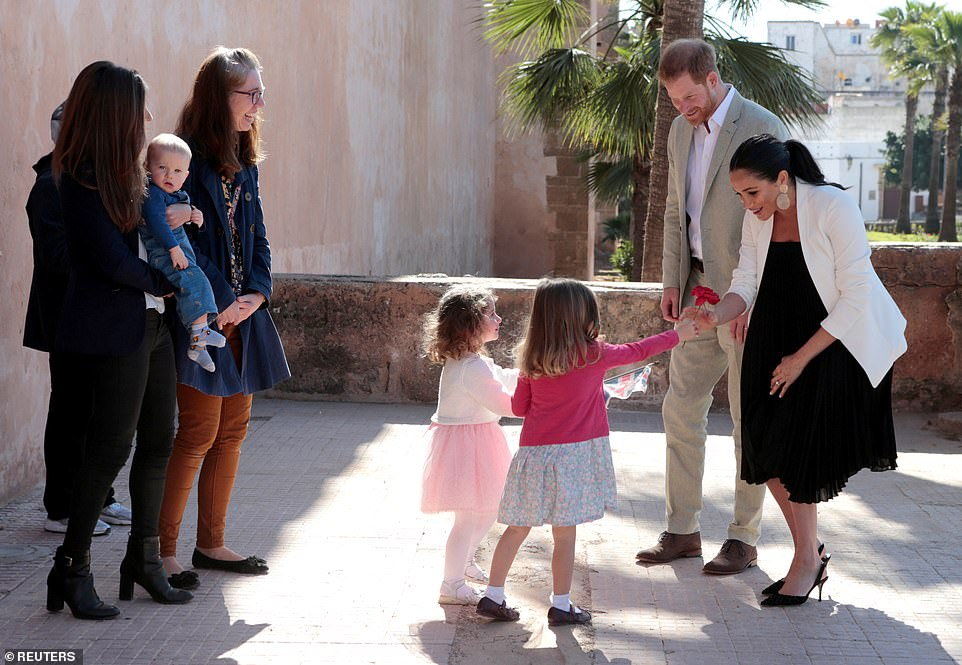 Later, on a visit to the Andalusian Gardens in Rabat, Meghan wore a more formal outfit. The couple were welcomed to the gardens by three-year-oldImogen and Tabitha who presented a delighted Meghan with a rose upon her arrival