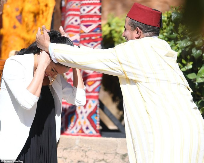 The mother-to-be bowed her head as the gentlemen helped her to put the wooden pendent around her neck