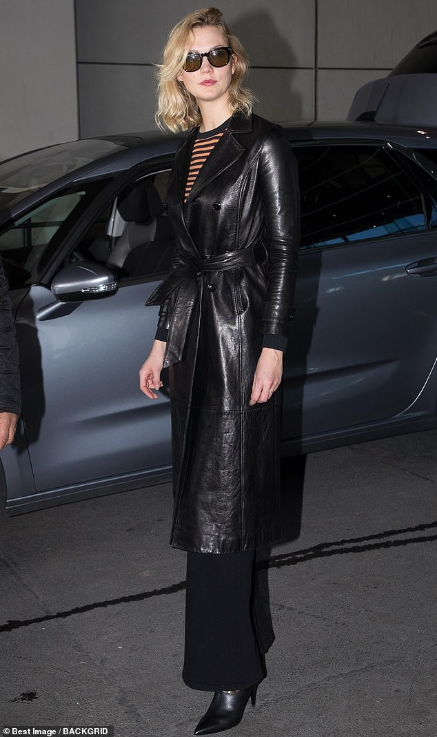 Hell for leather:The supermodel, 26, looked chic in a Matrix-style belted leather mac and tortoiseshell shades