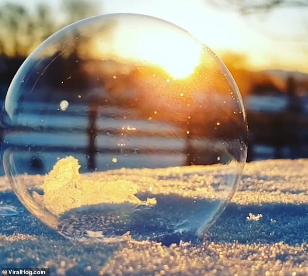 Tanya Stafford blows a bubble on to an icy surface during a freezing morning in Reno, Nevada