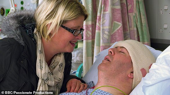 Mr Williams' wife Vicky is pictured visiting him after surgery to fit the implant