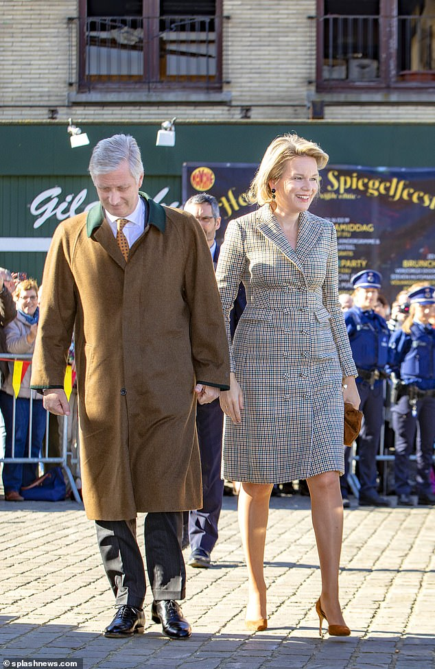 Not unlike his wife, King Philippe wore a dark brown overcoat with stand-out green trimmingsduring a visit to Herentals, Antwerp on Tuesday