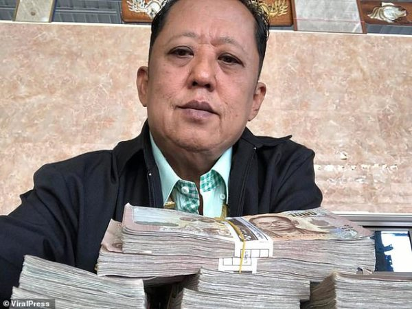 Show me the money: The 58-year-old millionaire farmer poses with wads of cash