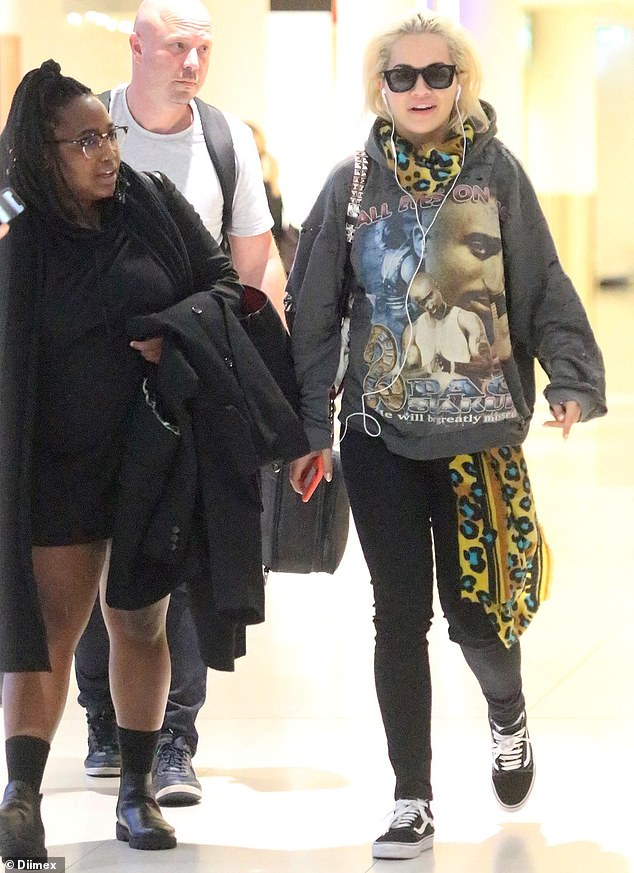 Low key: Rita looked casual in a Tupac Shakur sweater and skinny jeans as she walked across the airport