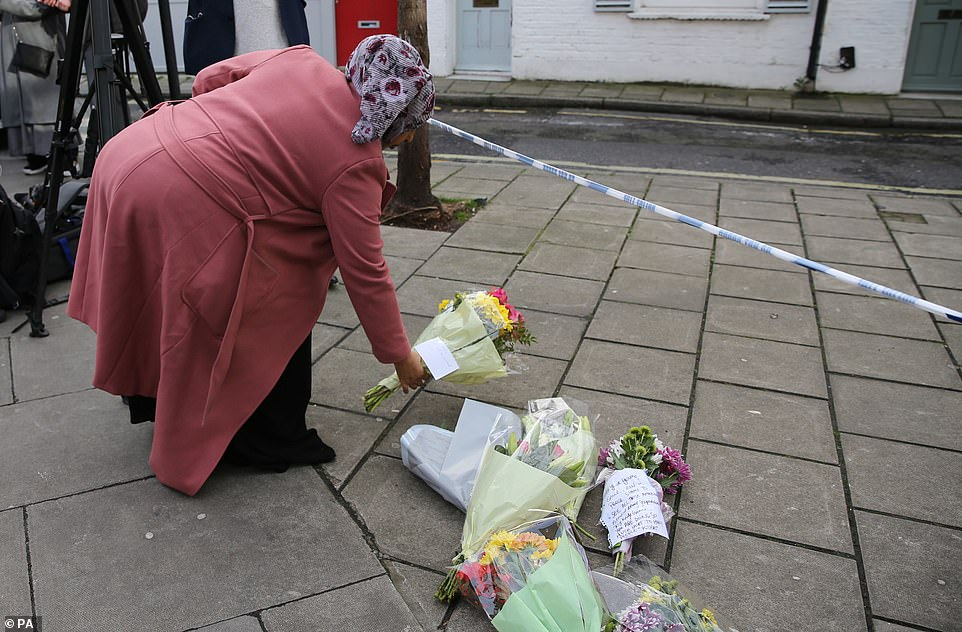 Mrs Osman leaves adds to the bouquets of flowers that are piling up in Lanfrey Place in memory of Mr Hassan, who she said was 'ambitious and handsome'