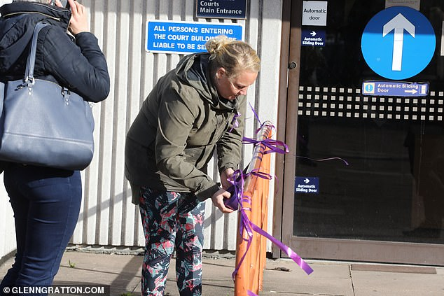 One woman, ties a purple ribbon on a railings outside of Barkingside Magistrates Court today where the suspect was charged