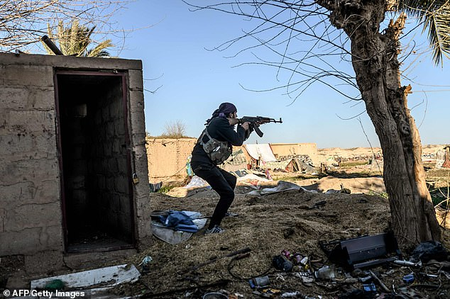 A Syrian Democratic Forces (SDF) fighter takes aim with his Kalashnikov rifle after seeing a man walking towards his position in Baghouz as the bid to push militants out of their last stronghold continues