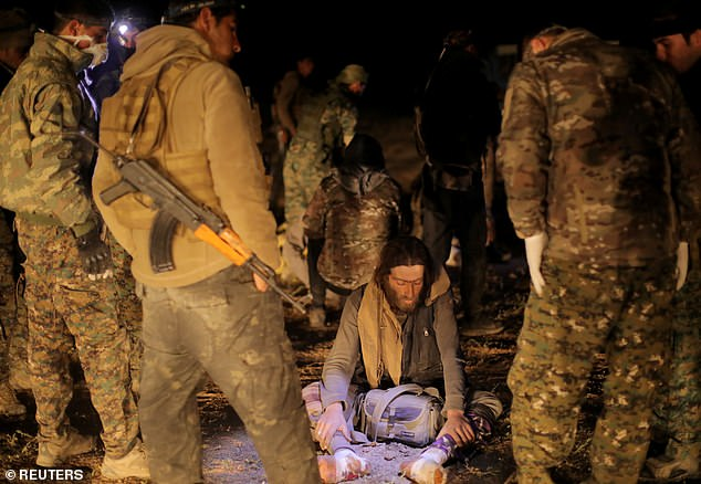 Fighters from the Syrian Democratic Forces (SDF) standing near a civilian who was evacuated from the fighting near the village of Baghouz