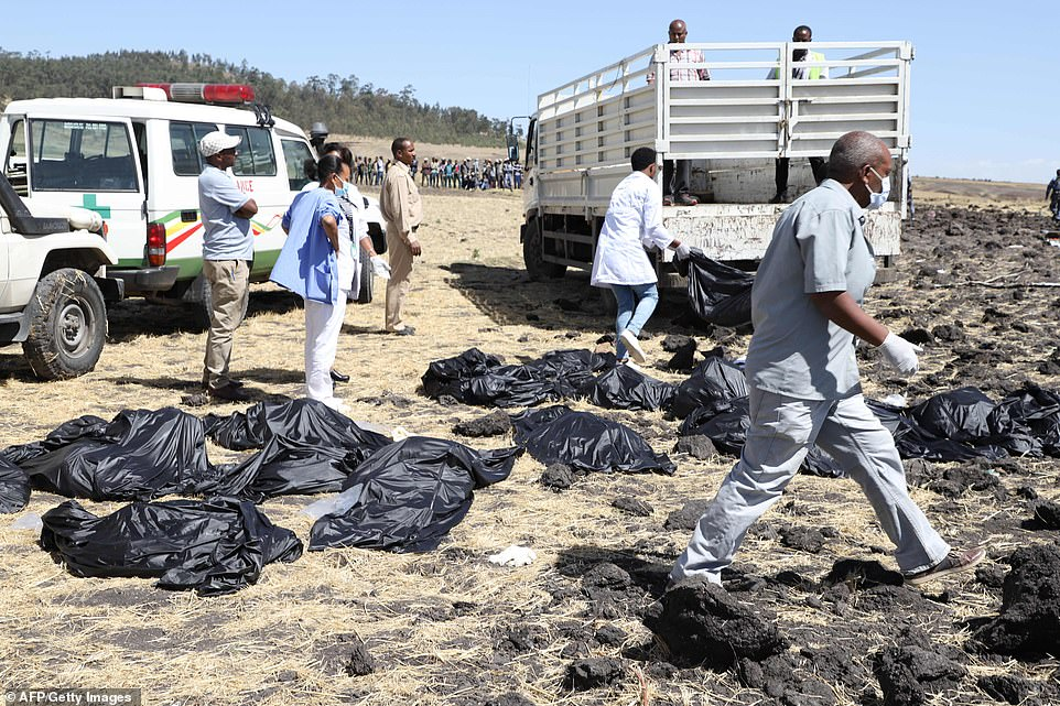 Rescue team walk past collected bodies in bags at the crash site of Ethiopia Airlines near Bishoftu, a town some 60 kilometres southeast of Addis Ababa