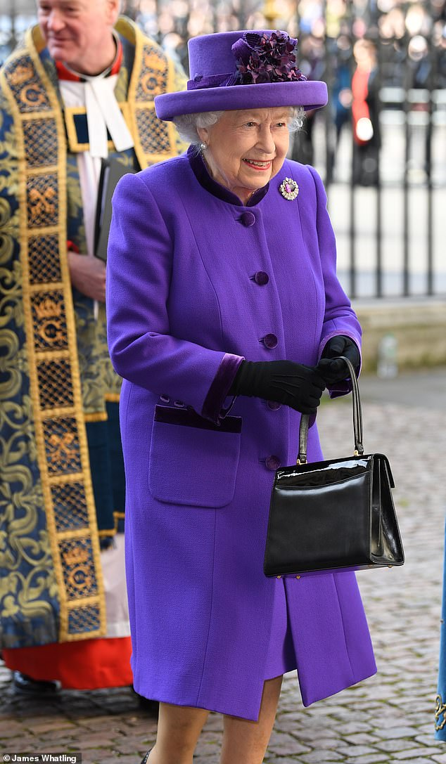 The Queen opted for a bold purple ensemble as she donned a matching hat and coat which she completed with a silver jeweled broach and a patent black bag (above)