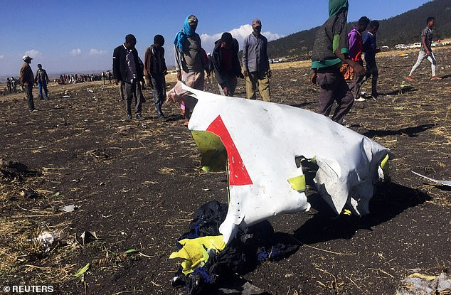 Debris from the plane is strewn around the area while locals comb the area for any signs of survival from the crash