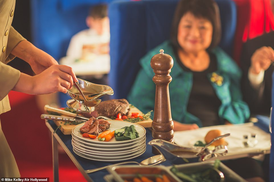 Mouth-watering: A stewardess serves guests their main courses at the Pan Am Experience