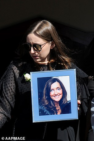 Sarah Ristevski pictured during her mother's funeral procession, carrying her portrait