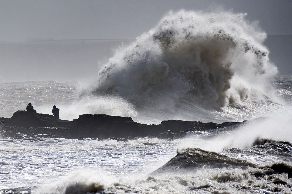 Waves are pictured crashing near the harbour in Porthcawl today as wind speeds surpass 50mph