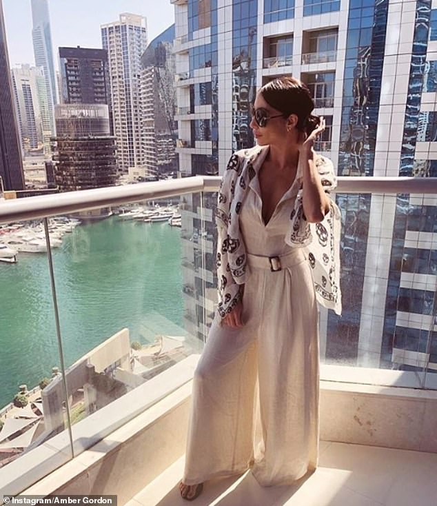 Amber sometimes has to fly just to approve a piece in person. Pictured, she wears Tom Ford sunglasses, Balenciaga sandals and a McQueen scarf for a photo in Dubai