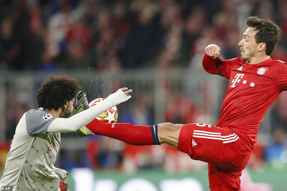 Liverpool forward Mohamed Salah tries to get out of the way of Hummels' high boot during the first half