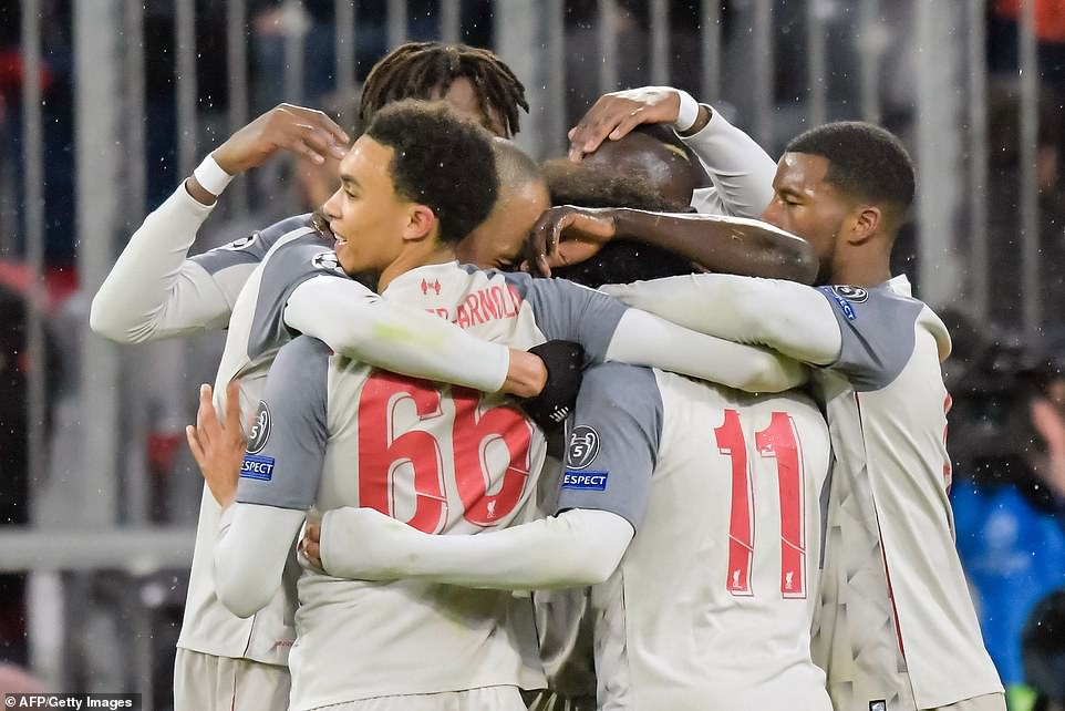 Mane is hugged by his Liverpool team-mates as his brace helped Liverpool sail into the quarter-finals of Champions League