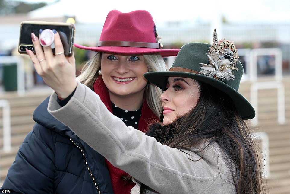 Time for a selfie: Two glamorous revellers pose for a photo, showing off their stylish trilbys with feather embellishment