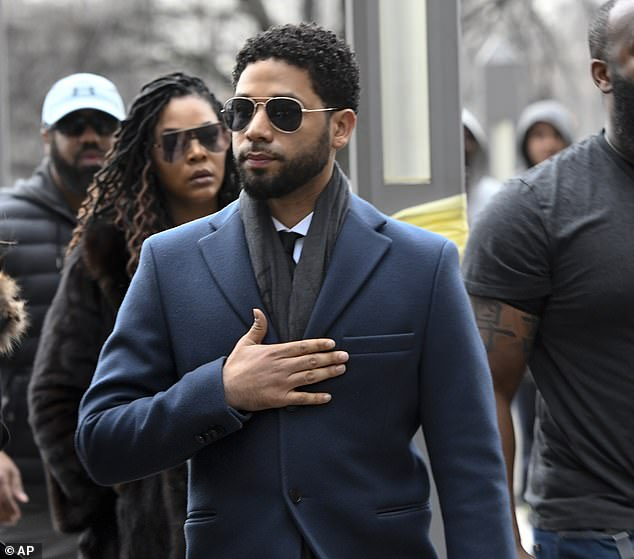 Jussie Smollett arrives in court in Chicago on Thursday to enter a plea on 16 counts of felony disorderly conduct. He put his hand on his heart as he walked past protesters shouting 'Justice for Jussie!'