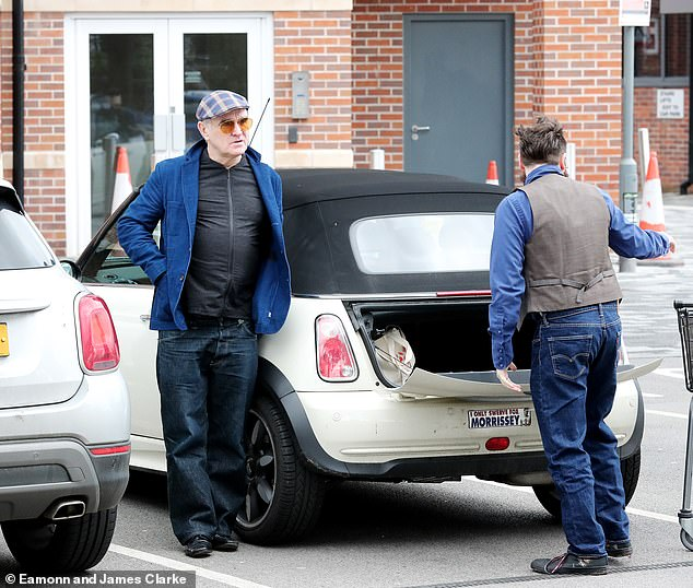Day out: Sporting a cap and a pair of tinted shades, he chatted to his friend as they packed the boot with groceries before taking off