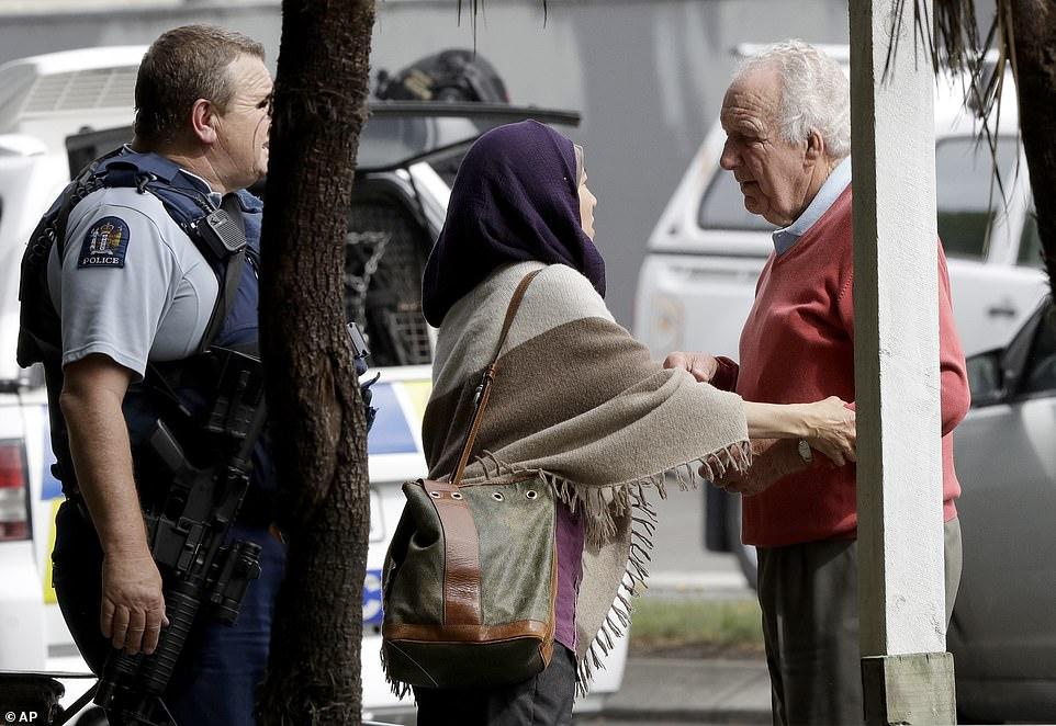 Police escort people away from outside one of the mosques targeting in the shooting